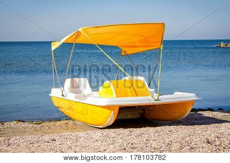 Yellow pedal catamaran boat with tent on a sea coast on a sunny day