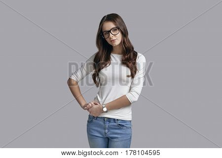 Confident in her style. Attractive young woman in casual wear keeping hands on hip and looking at camera while standing against grey background