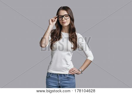 Beautiful and smart. Attractive young woman adjusting her thick rimmed glasses and looking at camera with a smile while standing against grey background