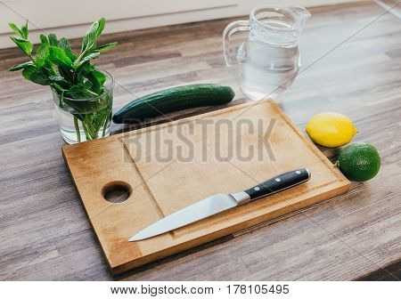 ingredients for infused water on a wooden table. Detox, diet concept. Lemon, lime, mint, cucumber and water in glass jug on table. Healthy drink