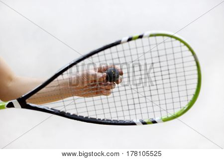 squash racket and ball in male hands. Racquetball equipment. Photo with selective focus. Player prepares to serve a squash ball. Closeup of hand serving ball