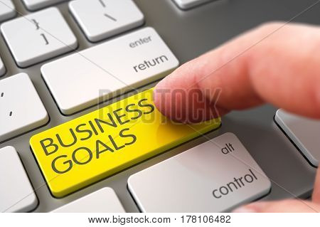 Man Finger Pushing Business Goals Yellow Key on Modern Keyboard. 3D Render.