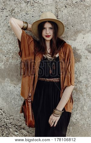 Stylish Boho Woman With Jewelry Posing At Rock Wall. Beautiful Hipster Gypsy Dressed Girl With Hat A