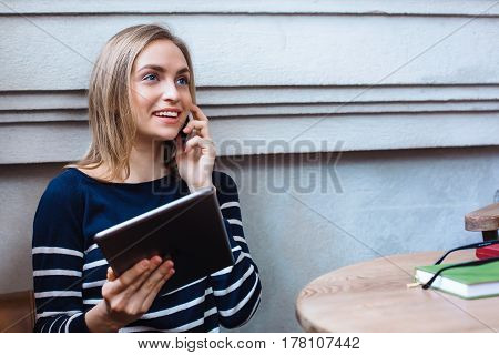 Happy female sitting in cafe and talking on mobile phone during work on touch pad young girl is surprised by what he saw tablet in hand having conversation on smartphone