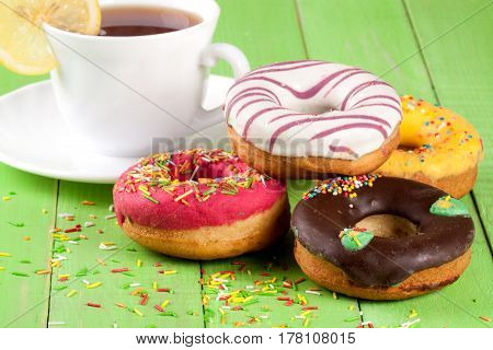 pile of glazed donuts with a cup of tea on a green wooden background.