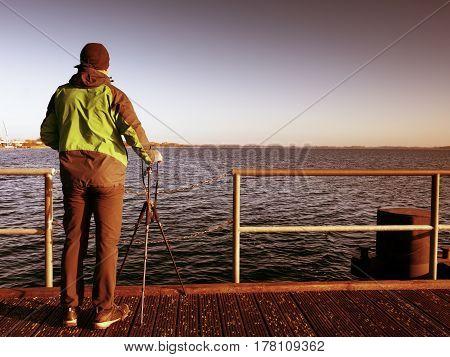 Alone Artist On Wooden Bridge. Photographer With Camera