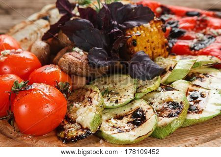 Delicious grilled vegetables. Tomatoes, red pepper, onion, zucchini, corn and mushrooms decorated with basil, close up view. Menu photo.