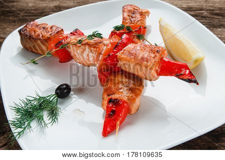 Appetizing salmon with tomatoes and chili pepper decorated with lemon on white plate, close up view. Japanese food.