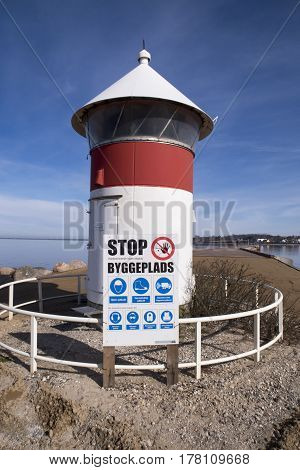 Old red and white lighthouse and building site warning sign close to Assens new harbor bridge in Denmark.