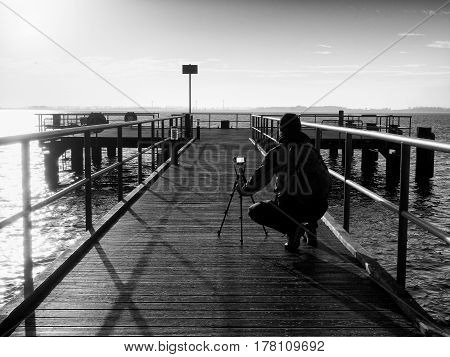 Tall nature photographer at tripod taking picture on the wooden pier in wharf at sunset time.