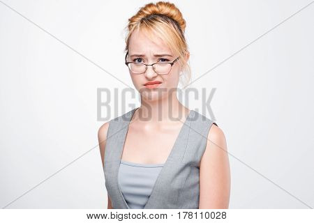 Young blonde in glasses shows contempt and neglect. Too high self-esteem, arrogance, disgust, non-acceptance, rejection.