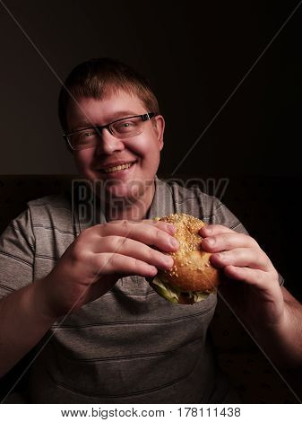 Lonely fat guy eating hamburger. Gluttony concept