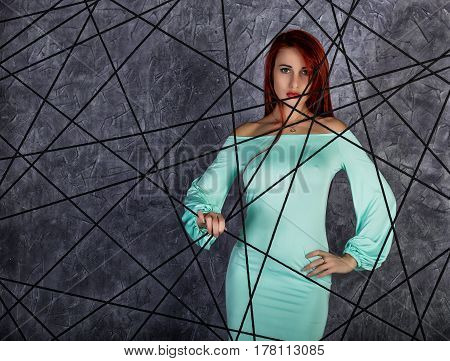 fashion portrait of redhead model posing near gray wall, girl with big tits in a tight dress.