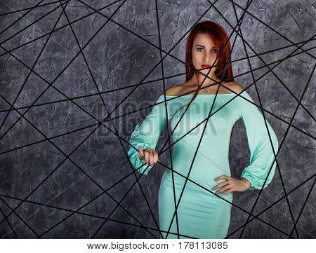 fashion portrait of redhead model posing near gray wall, girl with big tits in a tight dress.