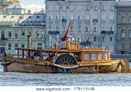 Vintage steam ship on the river Neva in the background of the waterfront