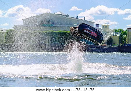 St. Petersburg, Russia. August 15, 2015. Flip athlete surfer with a spray of water against the embankment of the Neva river and historic buildings