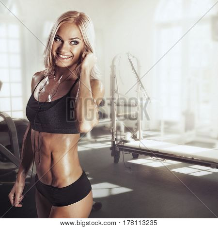 Girl with headphones relaxing in the gym