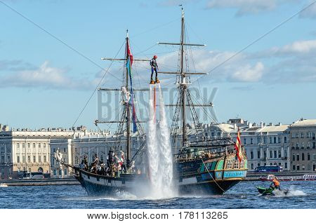 Russia, Saint Petersburg - August 15, 2015. Stylized pirate ship and athlete flavorlist next to it depict a fantastic battle scene at the sea festival in St. Petersburg. Summer, 2015.