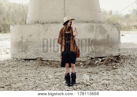 Stylish Hipster Woman In Hat And Fringe Poncho And Boots Posing Near River Stones. Boho Traveler Gir