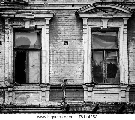 Two broken wooden windows on green brick facade of an old unkempt and vandalized house in Kiev (Kyiv) the capital of Ukraine. Black and white contrast image