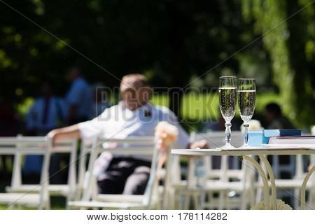 Two champagne glasses with bubbles standing on a table waiting for a wedding ceremony to begin on a bright sunny summer day outdoors in park with blurred sitting male guest in the background