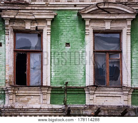 Two Broken Wooden Windows On Green Brick Facade Of An Old Unkempt And Vandalized House In Kiev (kyiv