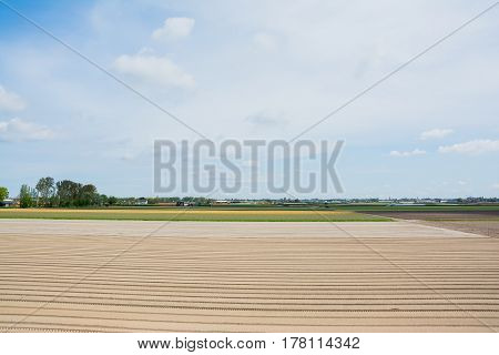 Empty field with furrows after tulips harvest prepared for planting in Keukenhof The Netherlands