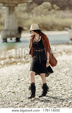 Stylish Boho Gypsy Woman In Hat, Fringe Poncho And Boots Walking On River Beach. Hipster Traveler Gi