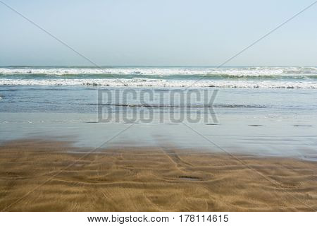 Sea Tidal Waves With White Foam On A Wet Sunny Sandy Beach In Resort On Summer Vacation. Background