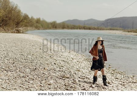 Stylish Boho Traveler Woman In Hat, Fringe Poncho And Boots Walking On River Beach, Boho Hipster Gir