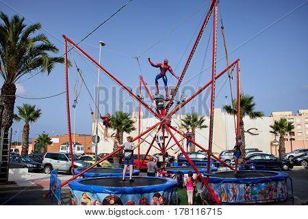 Guardamar del Segura, Spain - June 26, 2016: Children in the amusement Park jump high on the trampoline