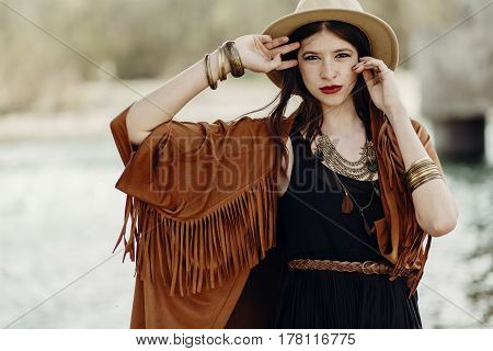 Stylish Hipster Woman Posing In Hat With Windy Hair, In Fringe Poncho And Accessory. Boho Traveler G