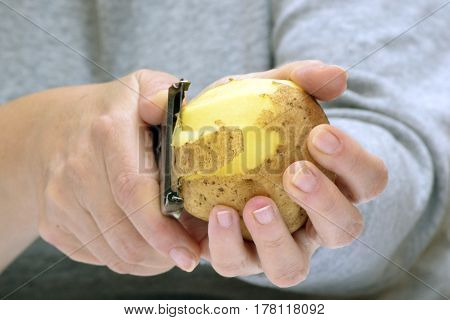 Female hands pell potato for a vegetable dish