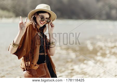 Stylish Hipster Boho Woman Smiling Showing Peace Sign In Sunglasses With Hat, Leather Bag, Fringe Po