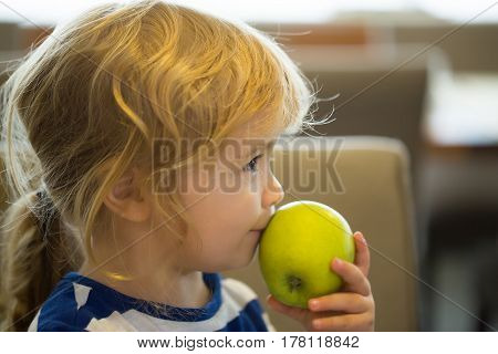 Cute baby boy little child with brown eyes and blond hair eating green apple natural vitamin healthy fruit food indoors