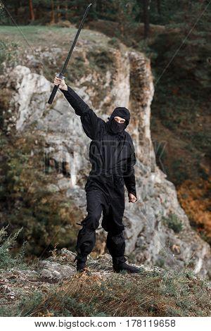 The assassin ninja sword crouched on cliff rocks in ambush