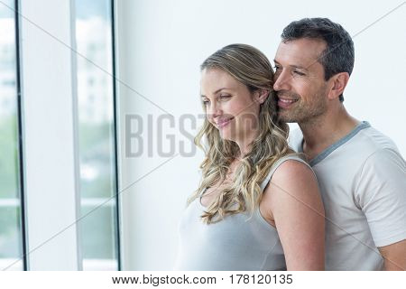 Couple looking away and smiling in bedroom