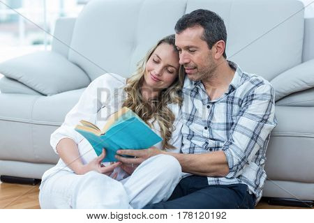 Expecting couple sitting on floor and reading book
