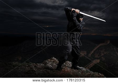 At night. Assassin ninja with sword on cliff waiting in ambush poster