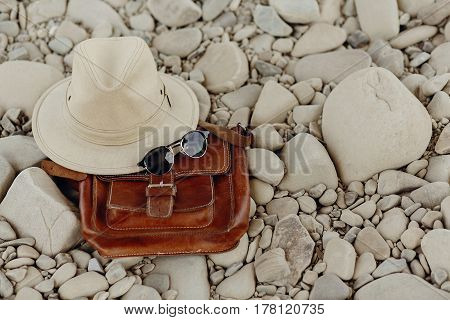 Wanderlust And Travel Concept. Stylish Hipster Hat And Sunglasses And Leather Bag On Beach With Spac