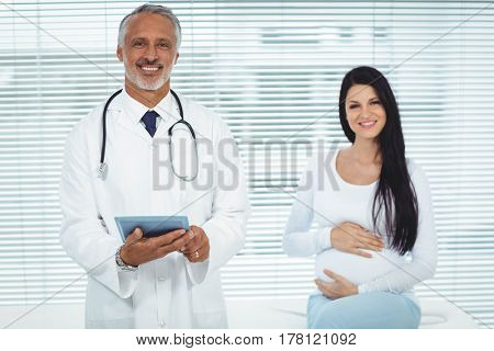 Doctor and pregnant woman smiling at camera in clinic