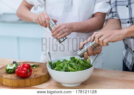 Pregnant couple preparing salad in kitchen