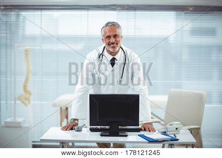 Portrait of doctor at his desk in clinic