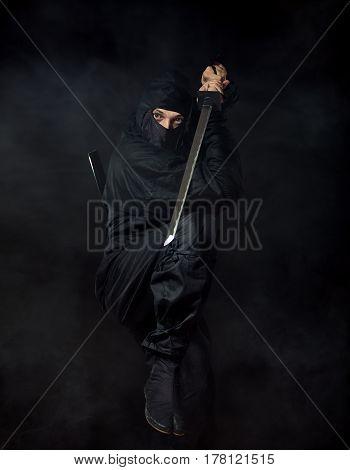 Ninja with sword at night in smoke