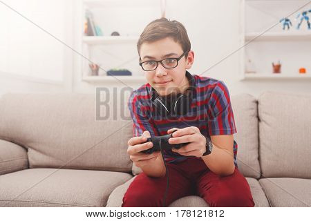Gaming video games concept - teenage boy playing football game with joystick and headphones, enjoying sitting on sofa in living room at home