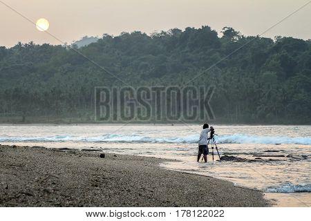 Cameraman capturing Sunrise  at Sawarna Beach, West Java Indonesia