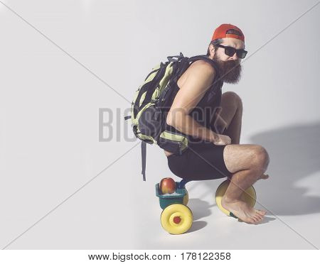 bearded man long beard brutal caucasian hipster with moustache in black vest sunglasses red cap with bag and apple has serious face sitting on colorfyl bicycle toy on grey background copy space