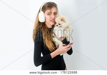 Pretty girl or beautiful woman in earmuffs holding cute pomeranian dog or puppy pet in woollen mittens and using smartphone mobile phone on white background copy space