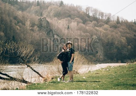 happy stylish hipster couple hugging and smiling at mountain river. wanderlust and travel concept. summer vacation and adventure.