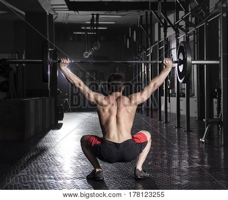 back view of strong crossfit athlete in a heavy overhead squat lift in a cross-fit  gym.Snatch exercise.